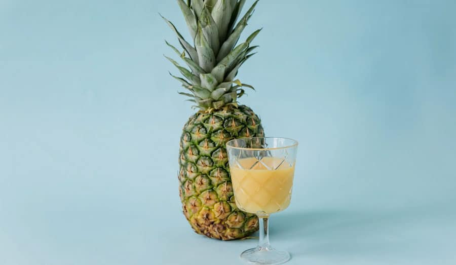fruity shake in a glass next to a whole pineapple